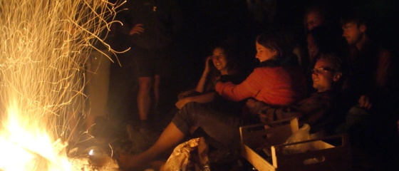 Picture 4: People sitting around campfire